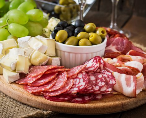 Cheese and cold cuts selection platter with black and green olives